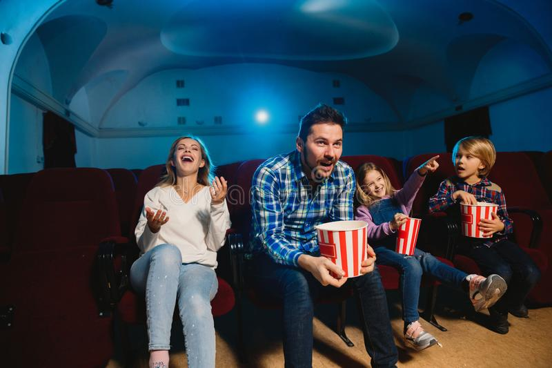 Young caucasian family watching a film at a movie theater stock photo