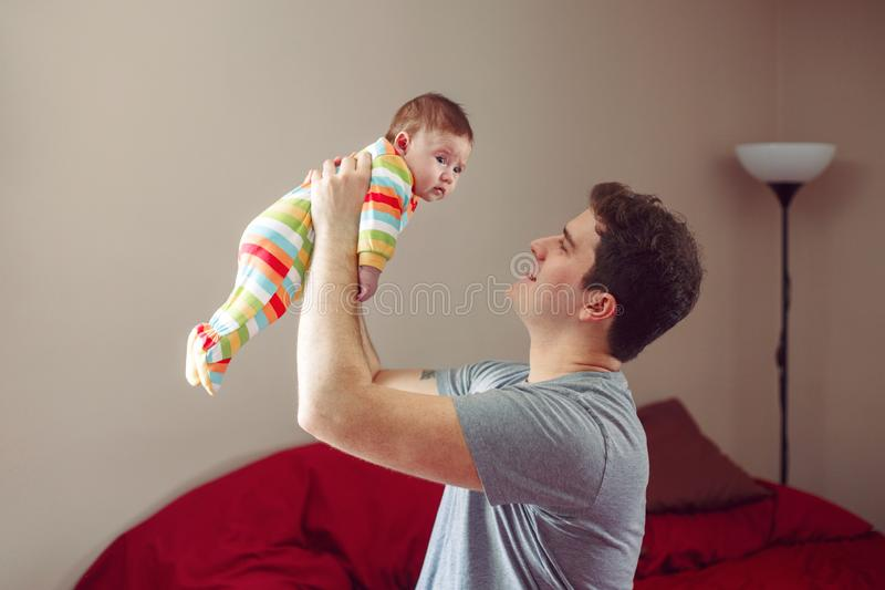 Caucasian father hugging and smiling talking to newborn baby. Male man parent holding child. stock photos