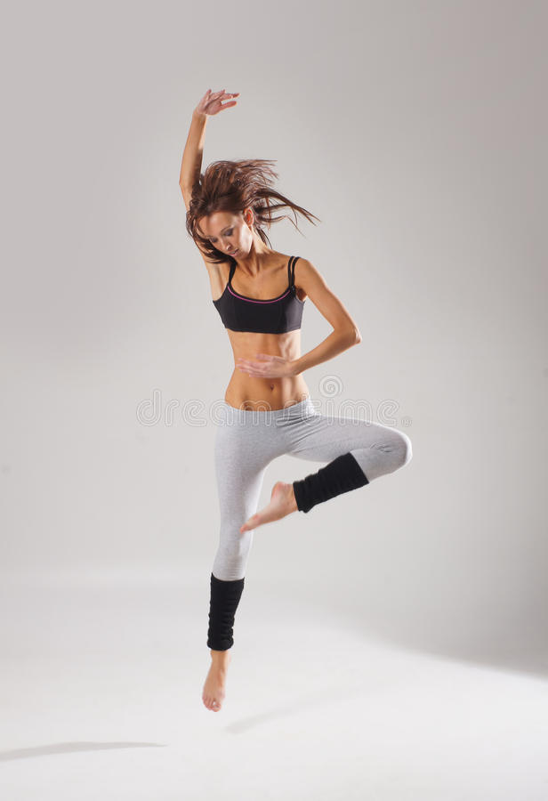 A young Caucasian female dancer caught in a jump royalty free stock photo