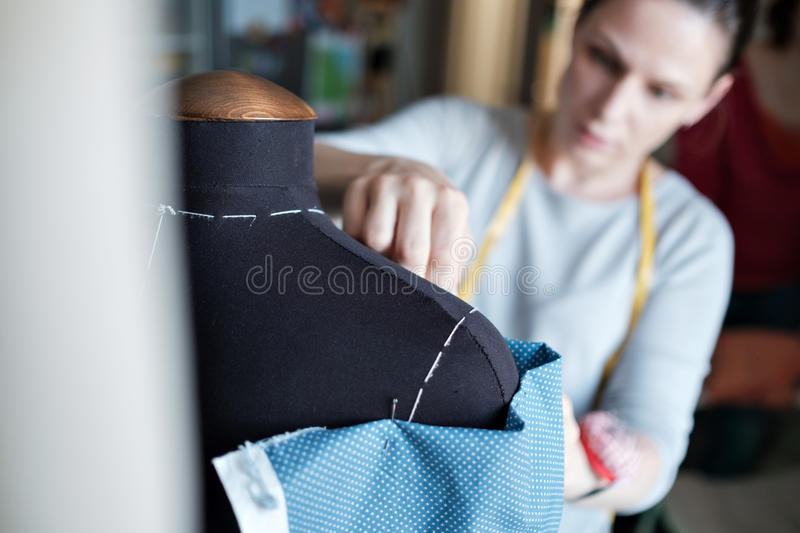 Young caucasian female fashion designer measuring a dress. stock photo