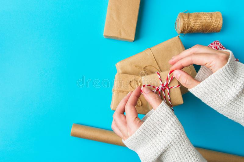 Young Caucasian female hands wrapping Christmas new Years gift boxes roll of brown Kraft ribbon on blue background. Holiday presents shopping stock images
