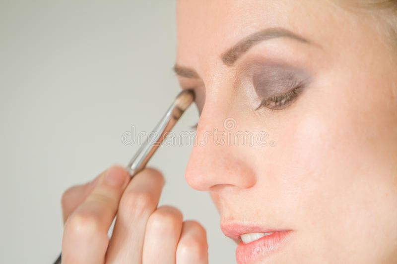 Young caucasian female model at a makeup. Applying make up to a royalty free stock photos