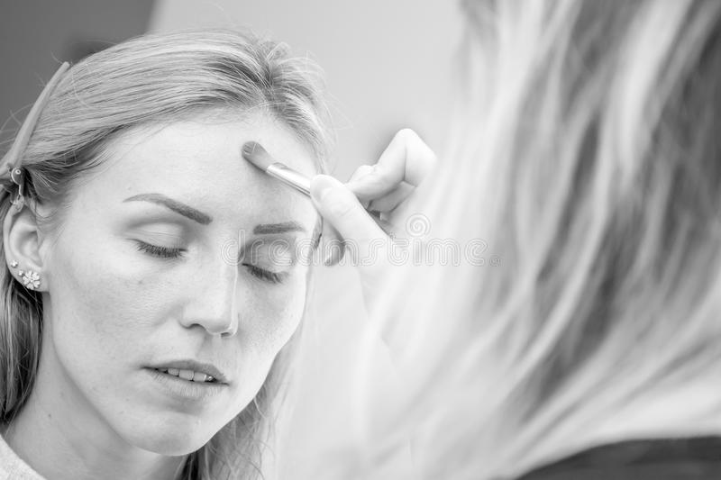 Young caucasian female model at a makeup. Applying make up to a stock image