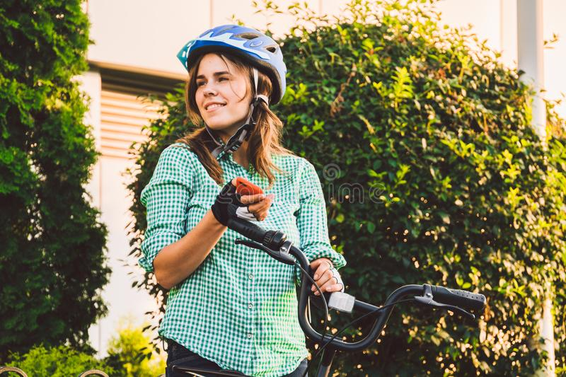 Young caucasian female student uses hand holding phone to touch screen. A woman stands near a rental city bike in sunny weather on stock images