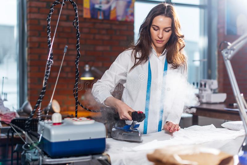 Young Caucasian female tailor ironing fabric with steam iron in a sewing workshop modern loft interior royalty free stock images