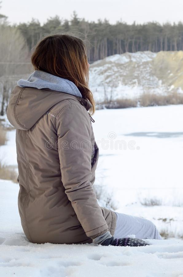 A young Caucasian girl in a brown coat staring into the distance on the horizon line stock photos