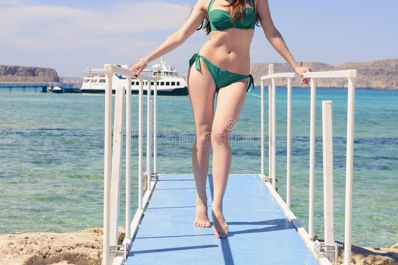 Young Caucasian girl in a green swimsuit on the blue pier, by background blue Ionian sea, Balos, Greece.  stock photography