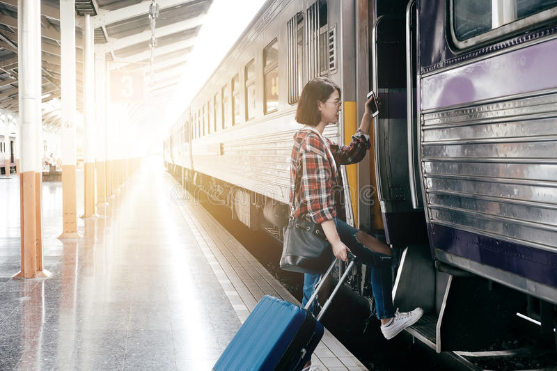 Young Caucasian girl with luggage at station traveling by train royalty free stock image