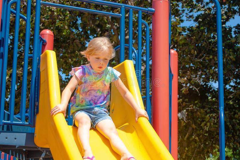 Young Caucasian girl on playground slide stock photography