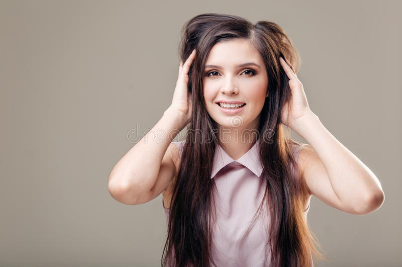 Young woman with hands in hair against grey background royalty free stock images