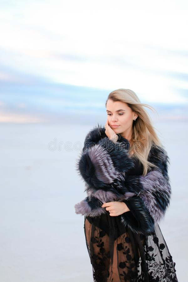 Young caucasian girl wearing black dress standing in white winter steppe background. royalty free stock photography