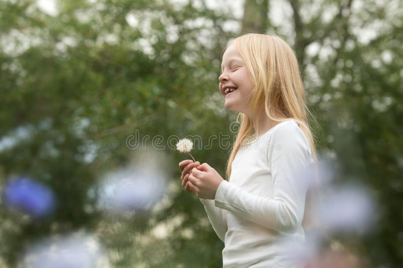 Young caucasian girl wishes on a dandelion stock photos