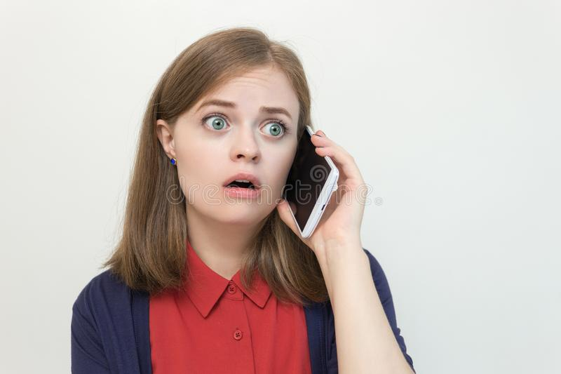 Young caucasian girl woman is talking on the mobile phone, looks scared, worried or sad royalty free stock images