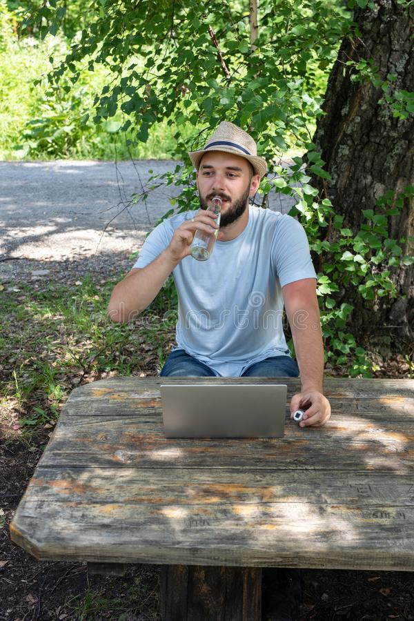 A young caucasian guy, a hipster is drinking clear water from a bottle. Hot weather on the street, thirsty. royalty free stock photos