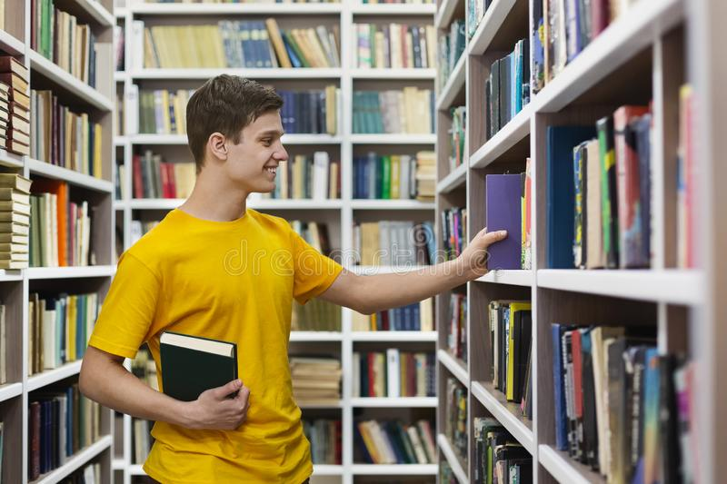 Young caucasian guy taking book from bookshelf. Young caucasian student taking book from bookshelf, studying at library, copy space stock images
