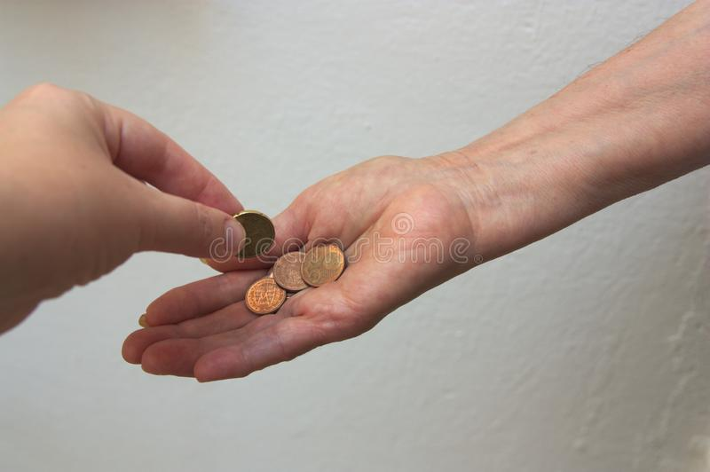A young Caucasian hand gives an elderly person alms stock photography