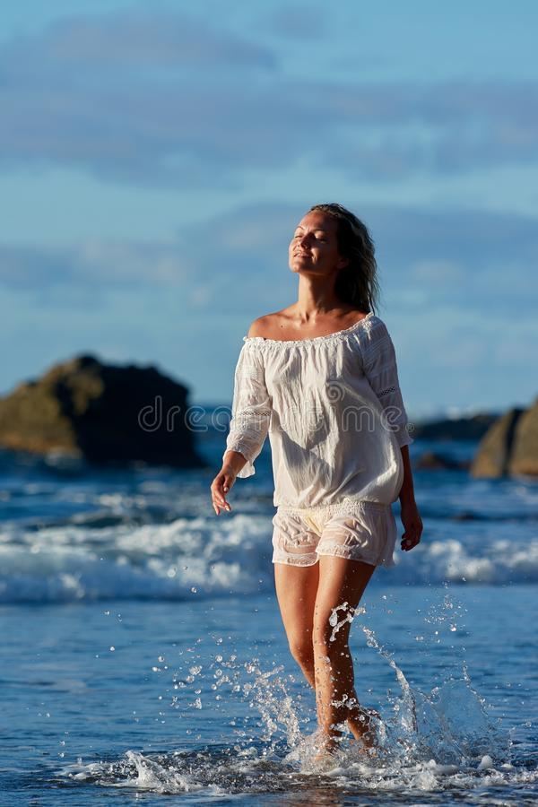 Young caucasian woman refreshing on the beach in summer evening royalty free stock photo