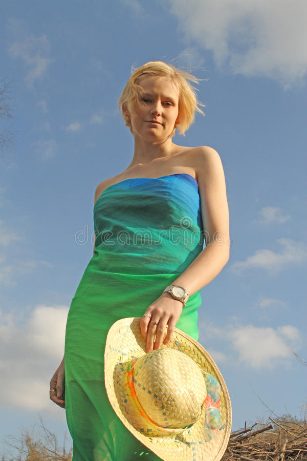 Young caucasian and hat portrait against bright sky. Young attractive blonde haired woman in bright clothing holding a summer hat looking thoughtful stock photography