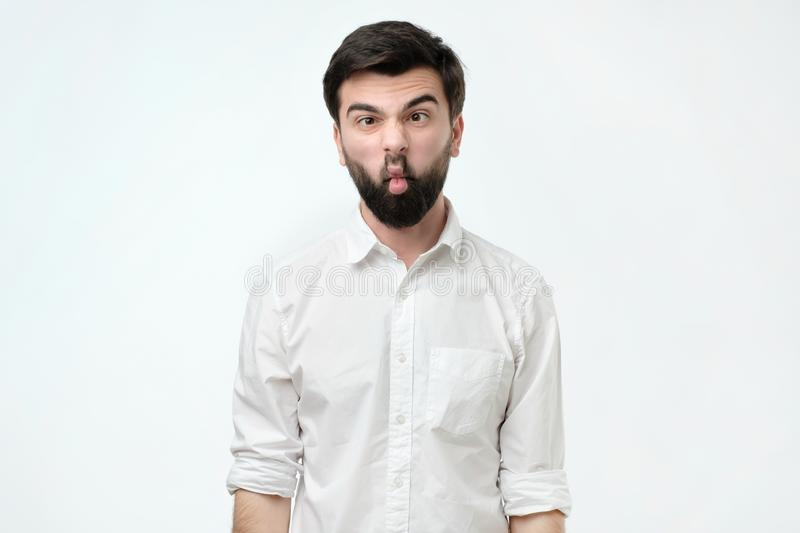 Young caucasian hipster man wearing white shirt over isolated background making fish face with lips royalty free stock images