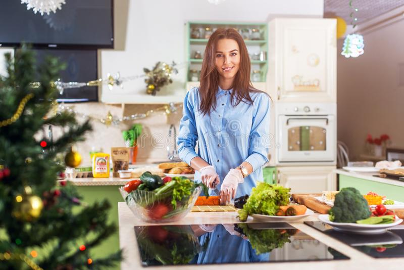 Young Caucasian lady cooking New Year or Christmas meal in decorated kitchen at home royalty free stock photo