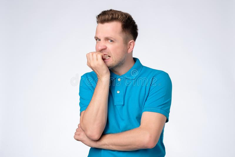 Young caucasian man in blue shirt biting nails being stressed or nervous. royalty free stock image