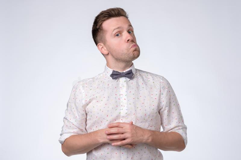 Young caucasian man in bow tie and funny shirt looking at camera with doubt. stock images