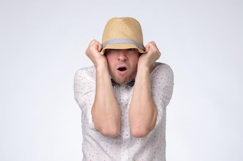 Young caucasian man closes face with hat trying to stay anonym. stock image