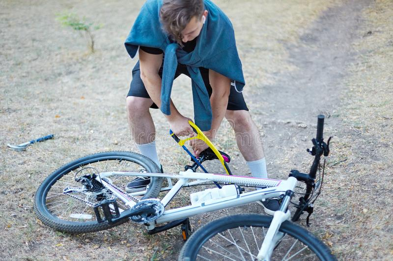 Young caucasian man with dark hair saws the bicycle laying on the ground in abandoned park with big blue and yellow hand saw. Fun, royalty free stock photo