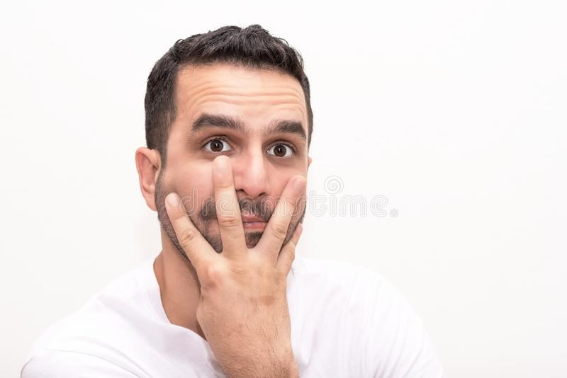 Young Caucasian man eith fingers on face stock image