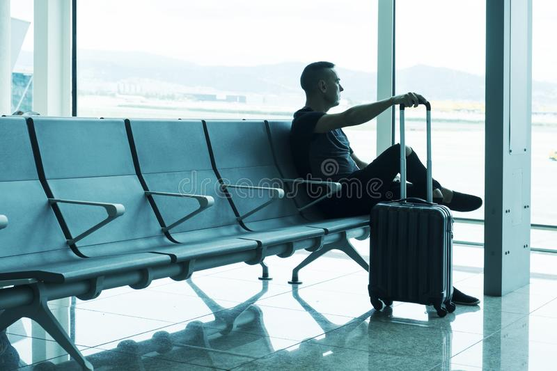 Man waiting for his flight in an airport. A young caucasian man, with his trolley case, waiting for his flight sitting at the waiting room of an airport stock image