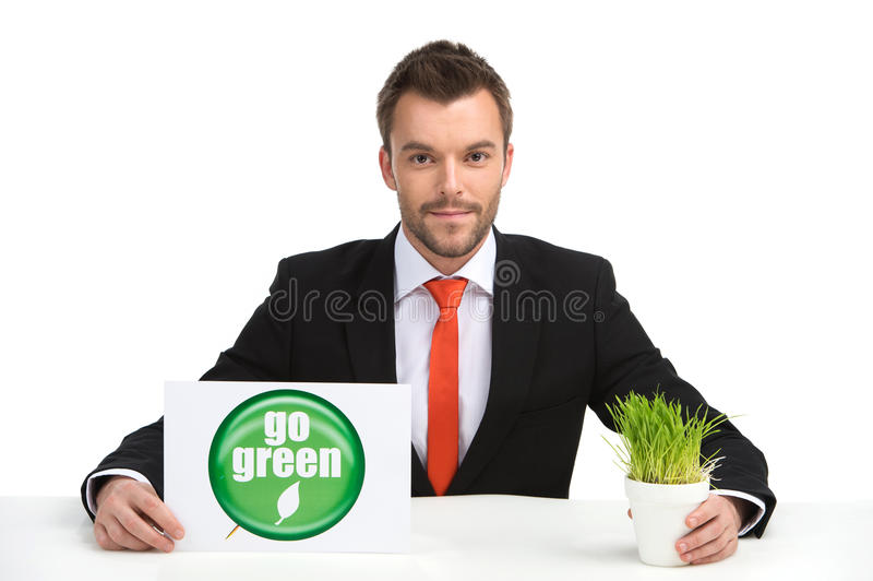 Young caucasian man holding go green sign and grass. stock photography