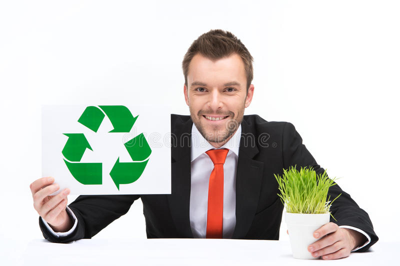 Young caucasian man holding recycle sign and grass. stock images