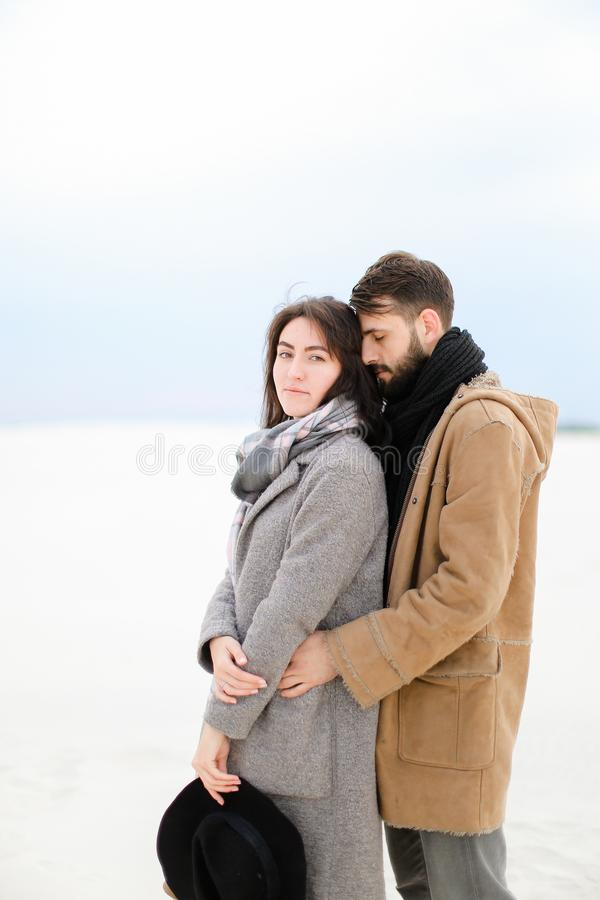 Young caucasian man hugging woman wearing grey coat and scarf in white winter background. Young caucasian men hugging women wearing grey coat and scarf in white stock photo