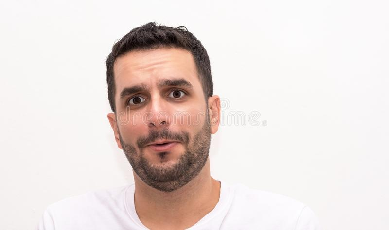 Young Caucasian man looks surprised, isolated stock photo