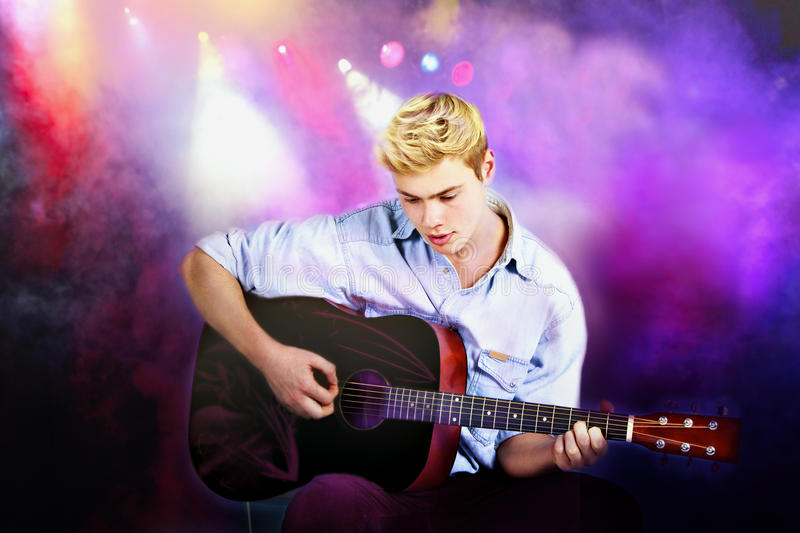 Young Caucasian man playing guitar in concert stock images