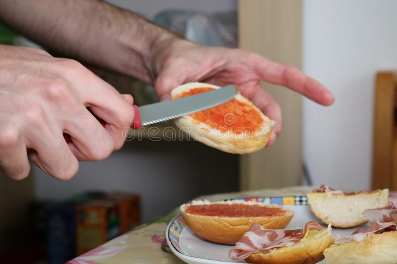 Young caucasian man prepares sandwich with Italian prosciutto and ketchup. Hand using knife close up stock image