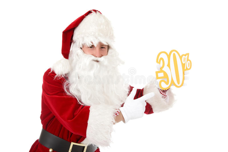 Young caucasian man Santa Claus, discount. Young caucasian man in Santa Claus clothes pointing at thirty percent discount sign. Studio shot. White background royalty free stock images