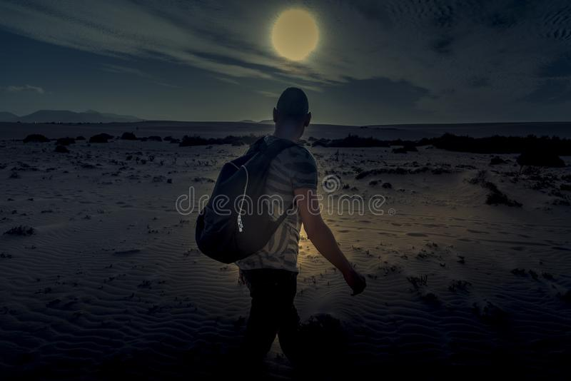 Man with a backpack walking in the desert. A young caucasian man seen from behind, carrying a backpack, walking by the sand of a desert, in backlit at dusk stock images