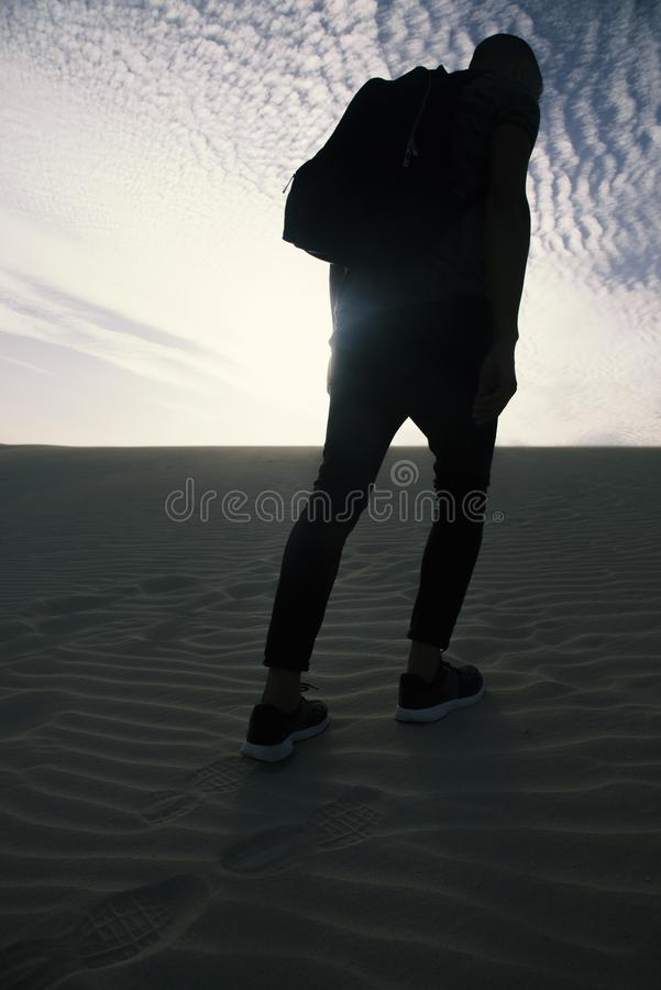 Man with a backpack walking in the desert royalty free stock photo