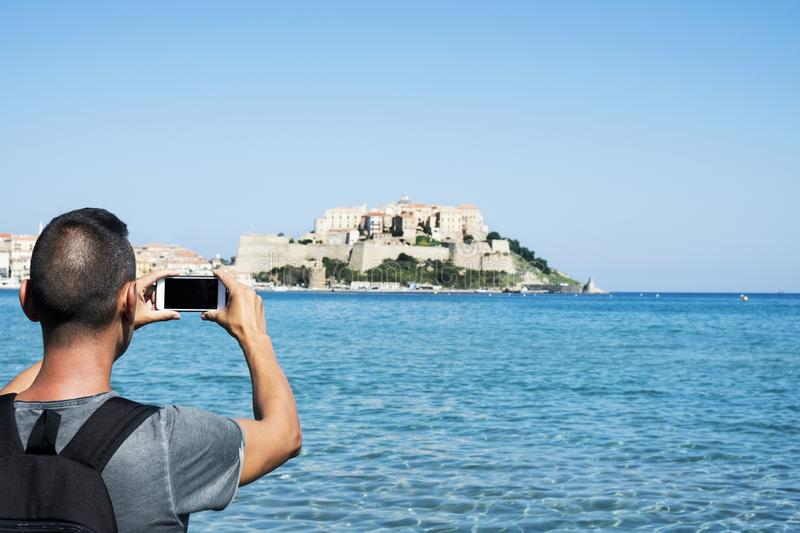 Man taking a picture of Calvi, in Corsica, France. A young caucasian man, seen from behind, taking a picture of Calvi, in Corsica, France, with the Mediterranean stock images
