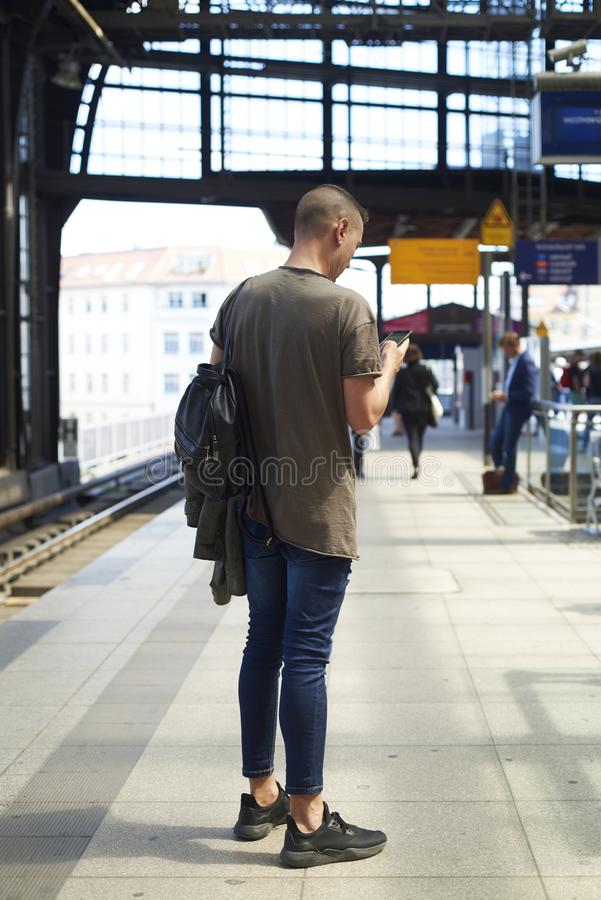 Man using smartphone in a train station in Berlin. A young caucasian man seen from behind using a smartphone in an outdoors train station in Berlin, Germany royalty free stock photography