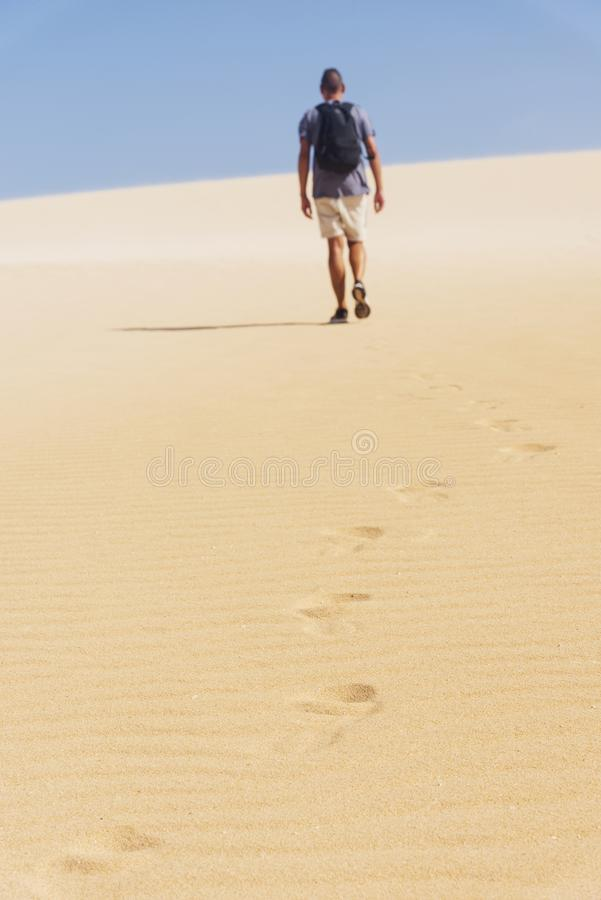 Young backpacker man walking by the desert. A young caucasian man, seen from behind, wearing a t-shirt and shorts, and carrying a backpack, walking by a white royalty free stock photos