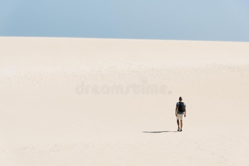 Young backpacker man walking by the desert. A young caucasian man, seen from behind, wearing a t-shirt and shorts, and carrying a backpack, walking by a white royalty free stock photography