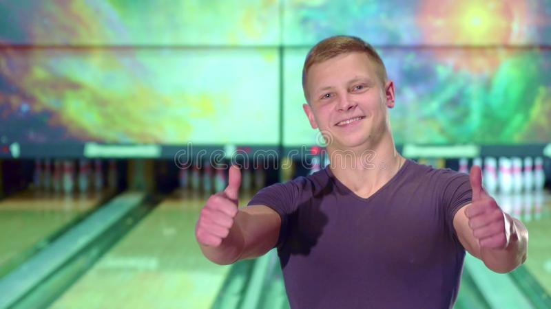Man shows his thumbs up at the bowling alley. Young caucasian man showing his thumbs up at the bowling alley. Blond boy taking ball from the floor. Attractive stock photography