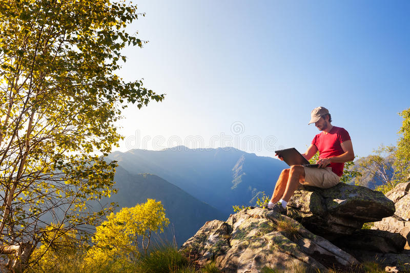 Young caucasian man sitting outdoor on a rock working on a laptop pc in mountain area. stock images