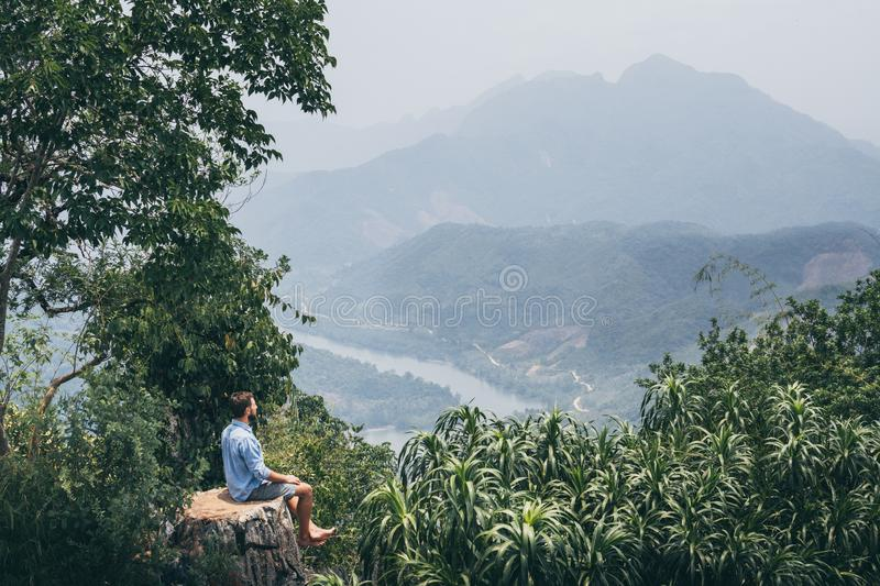Young Caucasian man sitting on the top of the mountain overlooking river valley in Nong Khiaw village, Laos. Young Caucasian man sits on the top of the mountain stock photos