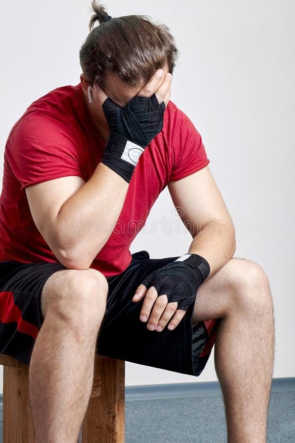 Young caucasian man in sportswear and boxing bandages sits with palm face. Despair moment, sorrow, hopelessness, despond before or. After match. Indoors, copy stock images