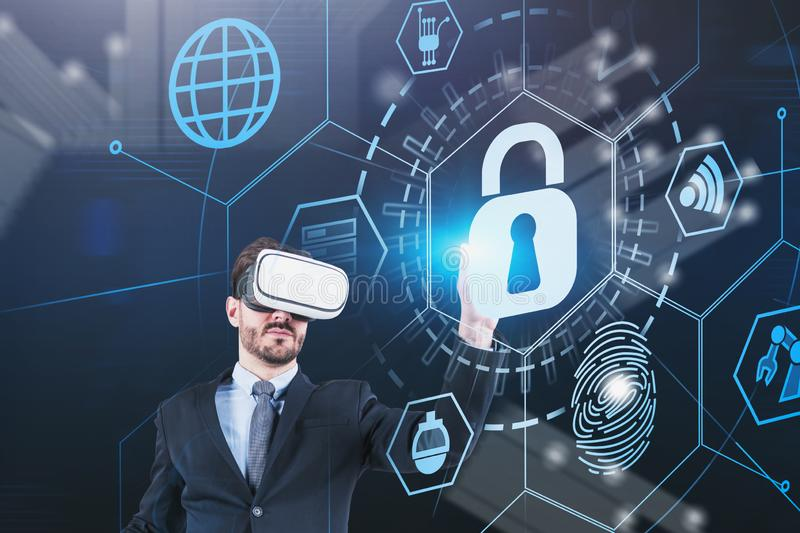 Man in VR glasses using online security interface. Young caucasian man in suit and VR glasses using online security HUD interface. Concept of data protection and royalty free stock image