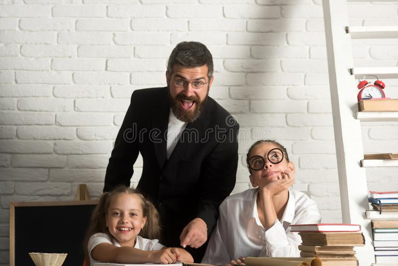 Young caucasian man teacher teach girls by using books and pens, education. stock photos