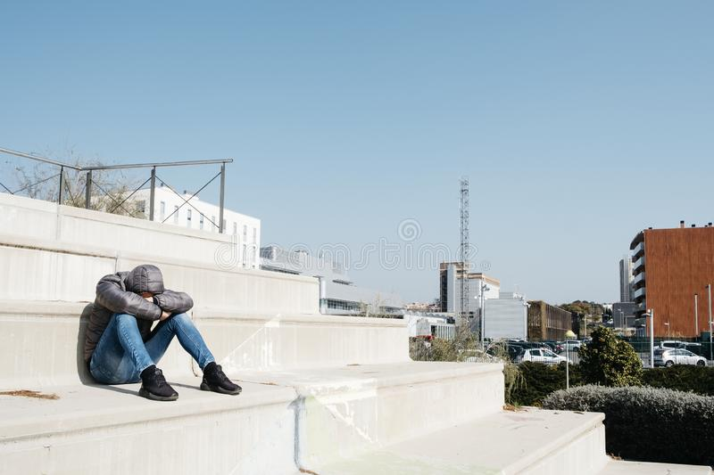 Man curled up sitting on an outdoor stairway. A young caucasian man, wearing jeans and a gray hooded jacket, curled up sitting on an outdoor stairway royalty free stock photography